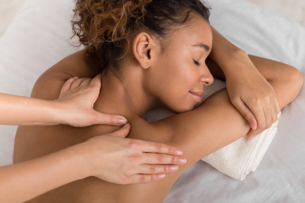 african-american woman enjoying shoulder massage in spa - massaggio foto e immagini stock