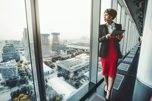 A good-looking African-American woman entrepreneur in a red skirt and black jacket is using a digital tablet while leaning against a panoramic window of a business office high-rise, cityscape outside