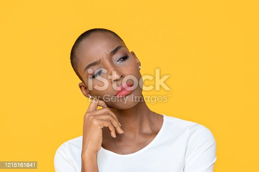 istock African-American woman feeling bored on yellow isolated studio background 1215161641