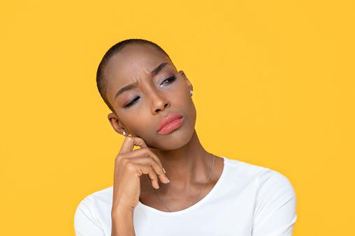 istock African-American woman feeling bored on yellow isolated studio background 1215161641