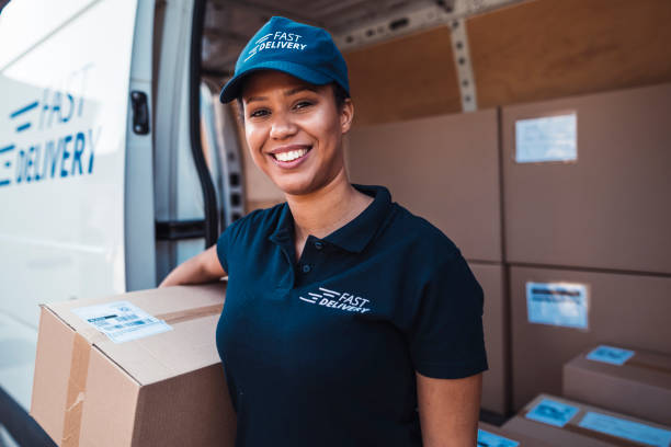 african-american woman holding a delivery package - postal worker стоковые фото и изображения