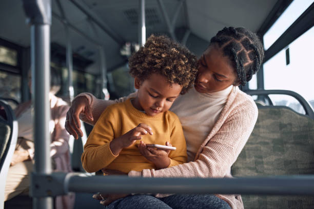 African-american woman holding boy playing with smartphone inside public bus stock photo