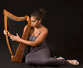 portrait of young beautiful woman with harp
