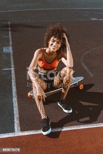 istock african-american woman on longboard 883679476