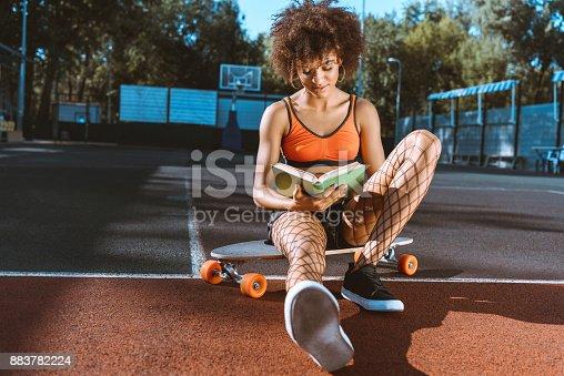istock african-american woman on longboard reading book 883782224