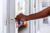 Close up of African-American woman unlocking entrance door with a key. Person using key and locking apartment door.