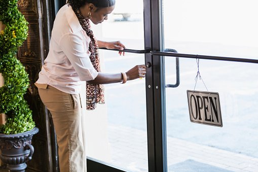 An African-American woman opening or closing a store, key in the lock in the door at the entrance. The door is glass, letting the sunlight through.