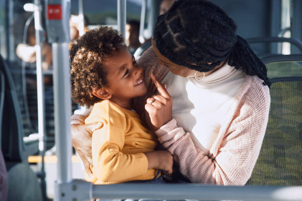 African-american woman playing with boy inside public bus stock photo