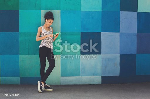 Happy smiling african-american woman leaning on bright blue graffiti wall, while listening music, relaxing from jog training, copy space