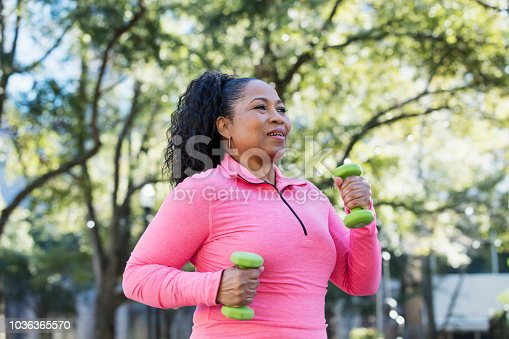 A senior African-American woman in her 60s exercising in the city. She is power walking with hand weights, wearing a pink sweatshirt.