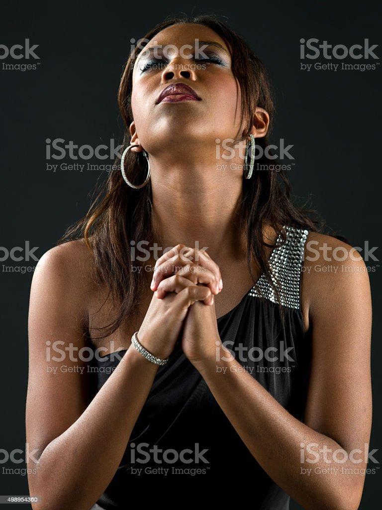 African-American woman praying upwards on black background. stock photo