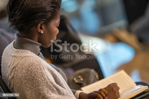 istock African-American woman reading a book while waiting for airplane 969396764