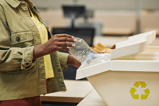 Close up of unrecognizable African-American woman putting plastic bottle into waste sorting bin in office, copy space