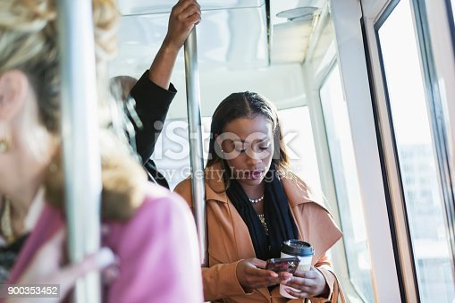 istock African-American woman riding train, texting 900353452