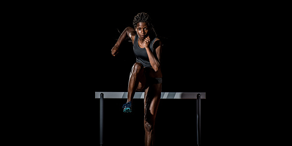 Front view of an African-American female athlete running away from a hurdle towards the camera.