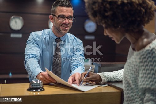 istock African-American woman signing hotel registration card 1074175908
