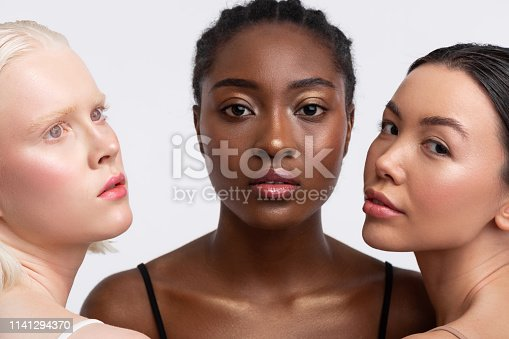 istock African-American woman standing between women with light skin 1141294370