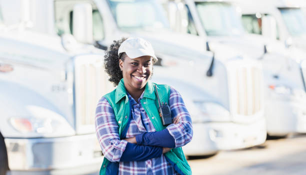 African-American woman standing in front of semi-trucks stock photo