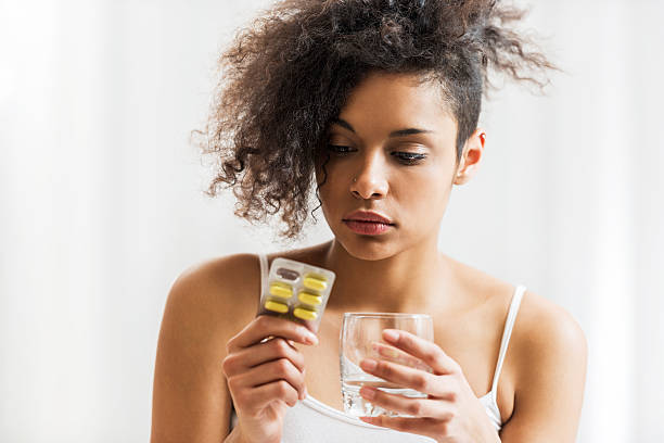 African-American woman taking medicine. Young African-American woman is holding pills and a glass of water. woman taking pills stock pictures, royalty-free photos & images