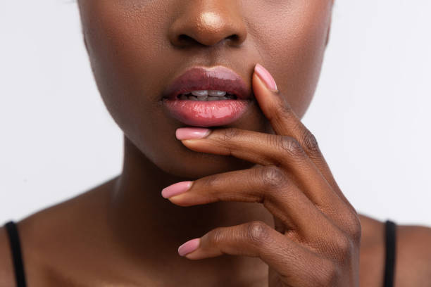 African-American woman touching lips with shiny lip gloss Shiny lip gloss. Close up of young African-American woman touching lips with shiny lip gloss human lips stock pictures, royalty-free photos & images