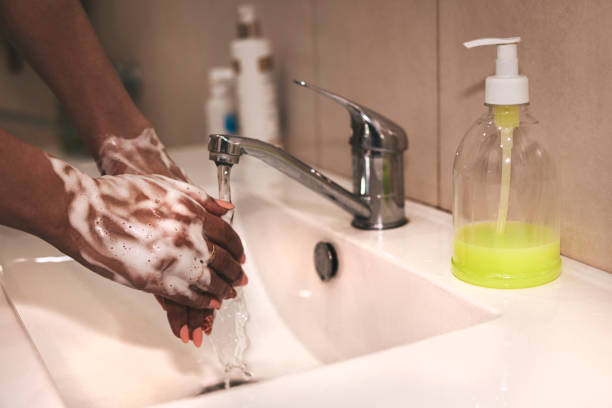 African-American woman washes hands. Cropped image of person washing hands at sink in bathroom, Coronavirus hand washing for clean hands hygiene Covid-19 spread prevention viral, bacterial infections stock photo