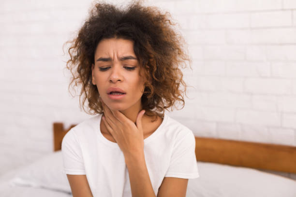African-american woman with sore throat sitting on bed African-american woman with sore throat sitting on bed in her bedroom heartburn throat pain stock pictures, royalty-free photos & images