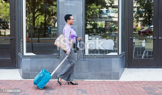 istock African-American woman with wheeled luggage in city 1129640262