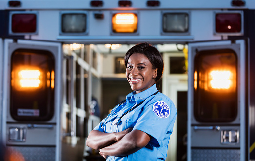 A young African-American woman standing, arms folded, smiling at the camera. The back of an ambulance with doors open and emergency lights on, is out of focus behind her. She is working as an EMT or paramedic.