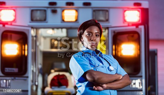 A young African-American woman standing with a serious expression, arms folded, looking at the camera. The back of an ambulance with doors open and emergency lights on, is out of focus behind her. She is working as an EMT or paramedic.
