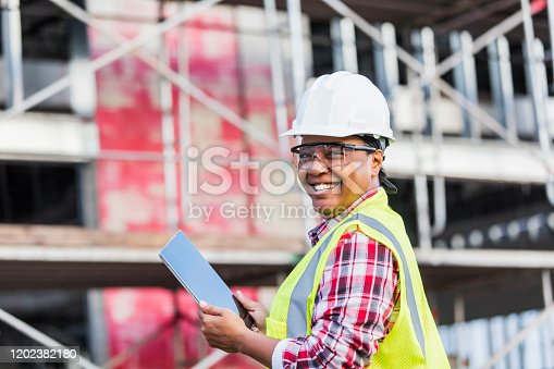 A mature African-American woman in her 40s working at a construction site, wearing a hardhat, safety goggles and reflective vest. She is looking over her shoulder at the camera with a confident expression, smiling, holding a digital tablet. A building under construction is out of focus in the background.
