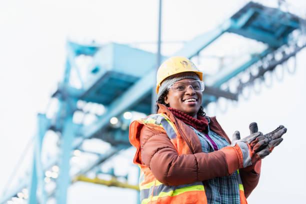 afro-amerikanische frau arbeitet im verschiffungshafen - arbeitshandschuhe stock-fotos und bilder