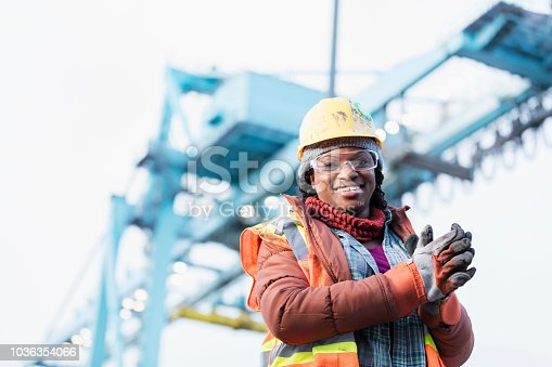 A mid adult African-American woman in her 30s wearing a hard hat, safety vest and safety goggles, a dock worker working at a shipping port. A gantry crane is out of focus in the background.