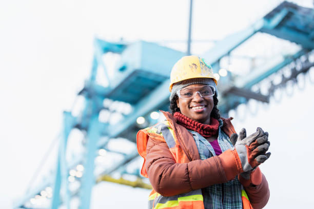 African-American woman working at shipping port A mid adult African-American woman in her 30s wearing a hard hat, safety vest and safety goggles, a dock worker working at a shipping port. A gantry crane is out of focus in the background. foreman stock pictures, royalty-free photos & images