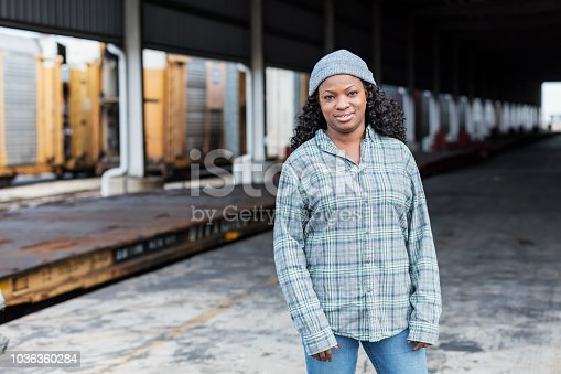 A mid adult African-American woman in her 30s working at a shipping port. She is a manual worker wearing a plaid shirt, jeans and knit cap, looking at the camera.