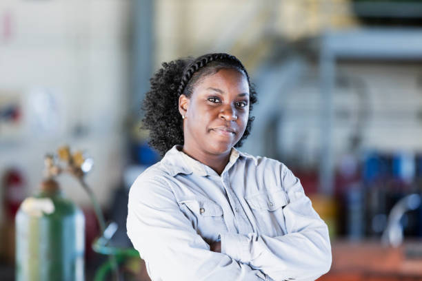 African-American woman working in repair shop stock photo
