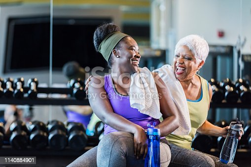 A senior African-American woman in her 60s exercising at the gym with her adult daughter, a young woman in her 20s. They are taking a break from lifting dumbbells, conversing and drinking from water bottles.