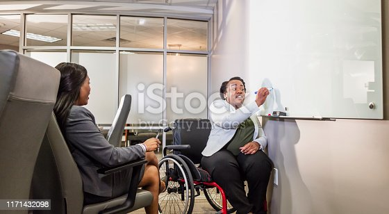 istock African-American women in boardroom, one in wheelchair 1171432098
