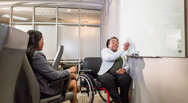 African-American women in boardroom, one in wheelchair Two African-American businesswomen having a meeting in a boardroom. The mid adult woman writing on the whiteboard is in a wheelchair. Her physical impairment is due to spina bifida. Her coworker, a mature woman in her 40s, is sitting, facing her. persons with disabilities stock pictures, royalty-free photos & images