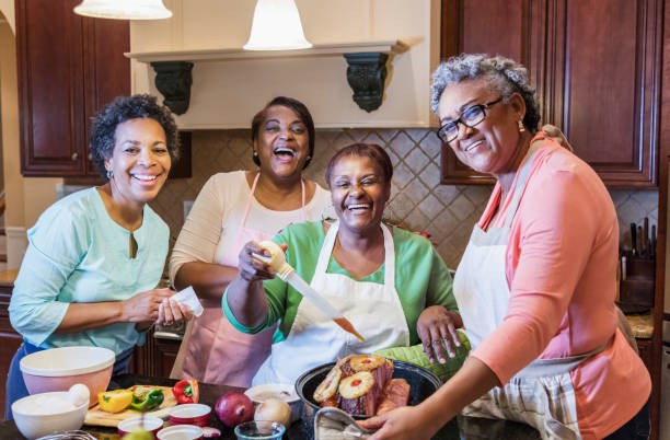African-American women in kitchen cooking stock photo