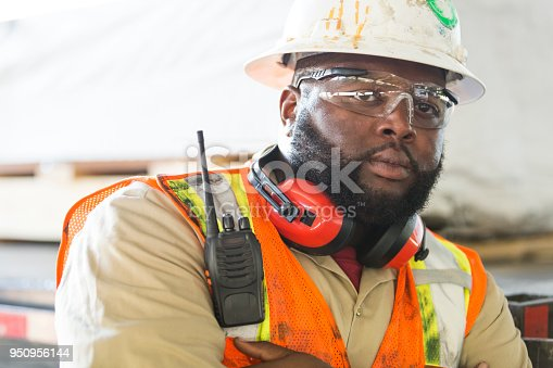 A mid adult African-American man in his 30s working, wearing a hardhat, safety goggles and reflective vest. He is a construction worker or engineer. His arms are crossed and he has a tough, serious expression on his face.