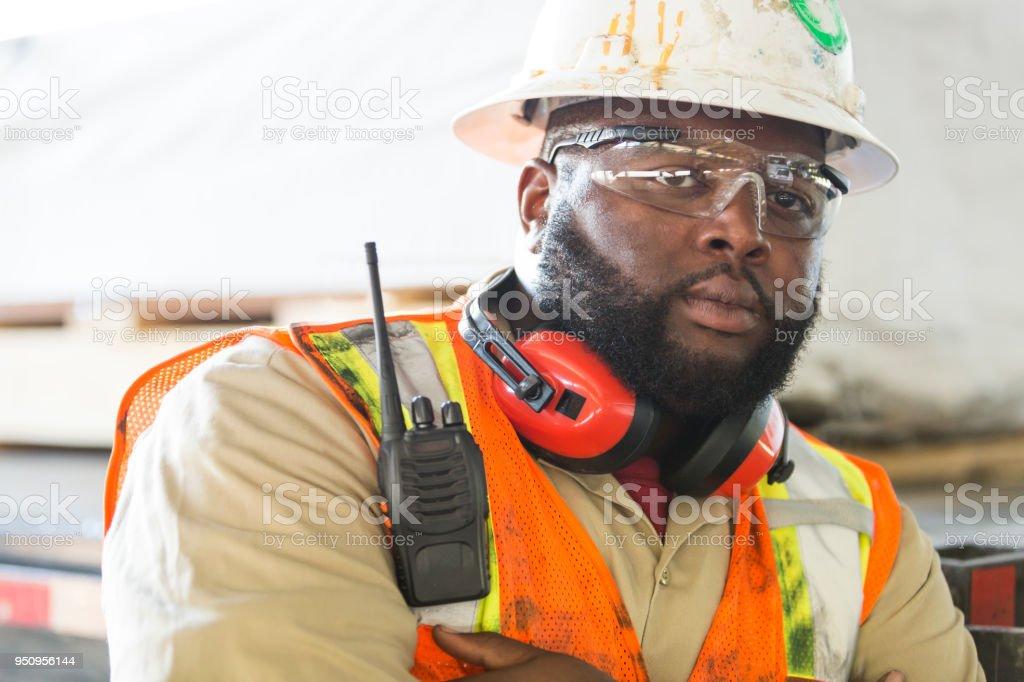Afroamerikanische Arbeiter in Bauarbeiterhelm, reflektierende Weste – Foto