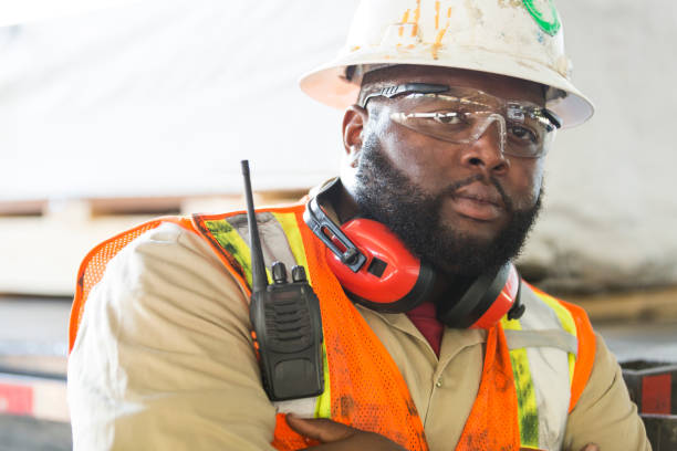 African-American worker in hardhat, reflective vest A mid adult African-American man in his 30s working, wearing a hardhat, safety goggles and reflective vest. He is a construction worker or engineer. His arms are crossed and he has a tough, serious expression on his face. protective eyewear stock pictures, royalty-free photos & images