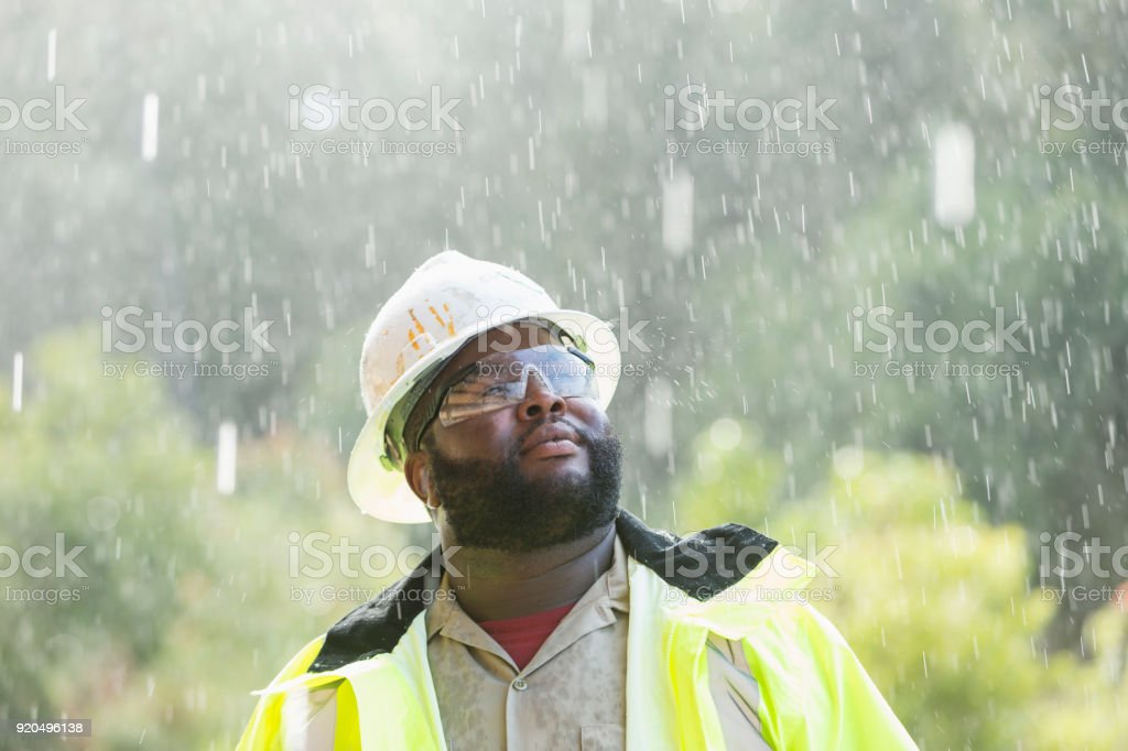 africanamerican worker standing in the rain stock photo more