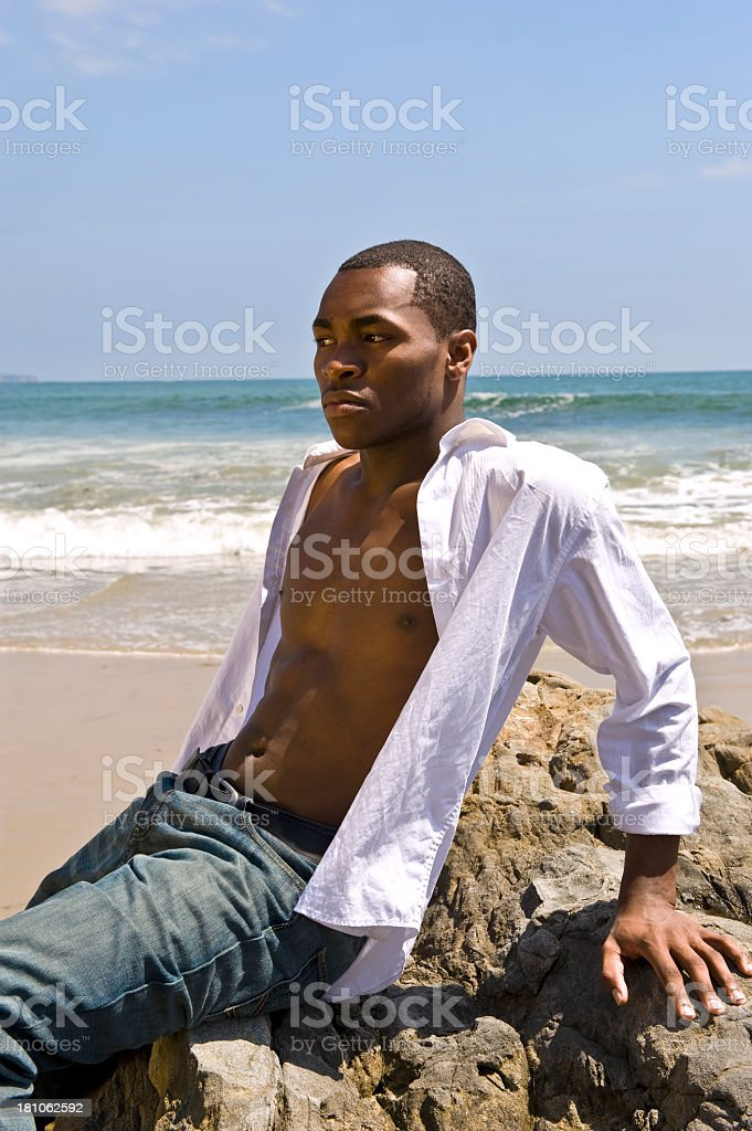 African-American Young Man Sitting on Rocks Near Ocean royalty-free stock photo