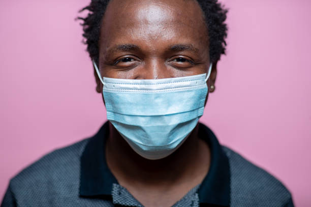 African-American young man with protective face mask smiling with eyes at camera stock photo