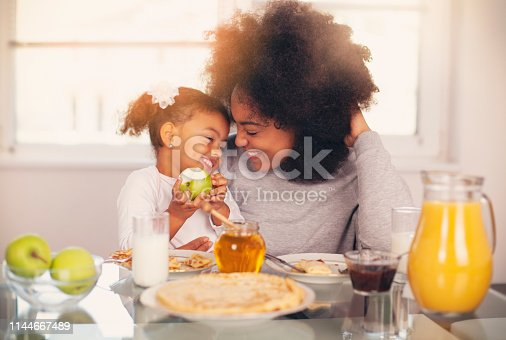 African-American young mother and daughter having breakfast