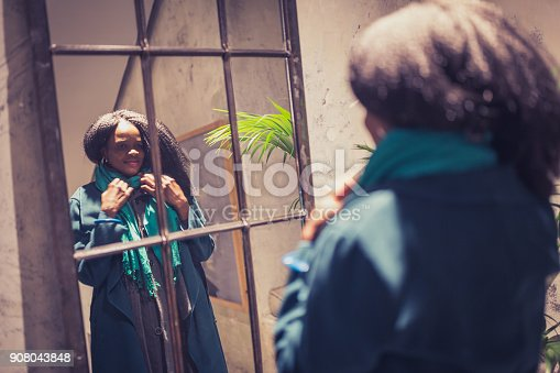 istock African-American young woman, fixing her coat in front of the mirror. Preparing for going out 908043848