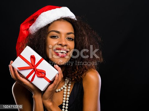 istock African-american young woman in party dress holding gift box with red ribbon and bow on black lights background. Girl smiling, she happy to get present on New Year or Christmas 1024712210