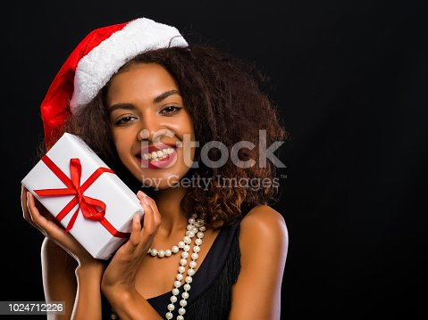 istock African-american young woman in party dress holding gift box with red ribbon and bow on black lights background. Girl smiling, she happy to get present on New Year or Christmas 1024712226