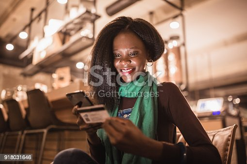 istock African-American young woman shopping on-line in cafe 918031646